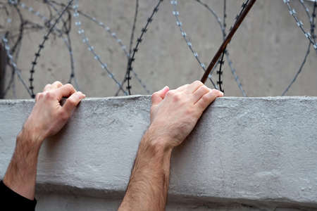 Men's hands on a concrete fence against a background of barbed wire. trying to escape from prison. The concept of escape from prison, guarding the territory from the intruders. illegally convicted