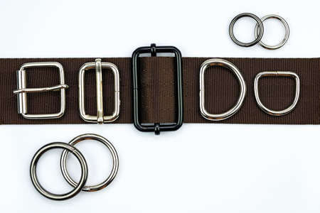 Brown belt with adjusters, buckles, rings, half rings top view. Metal bag accessories on a belt strap on a white background. Attachments for clothes and backpacks.
