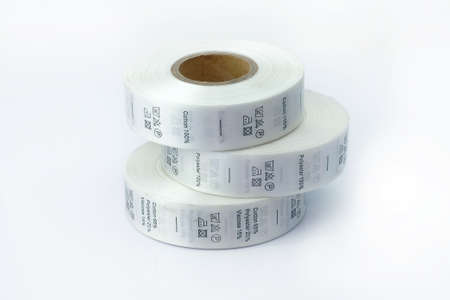 clothing care labels. Clothing labels, sewing accessories. White skeins, a roll of ribbon with information on washing and fabric composition.