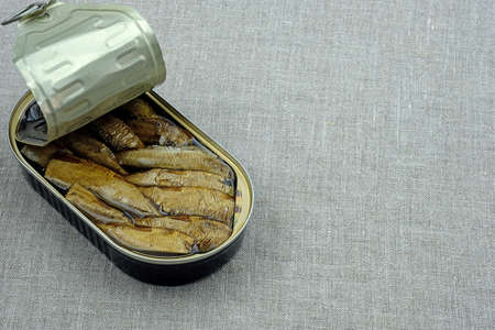 Canned sprats on a gray fabric background top view. Sprats in a tin can with a copy space. Canned fish.