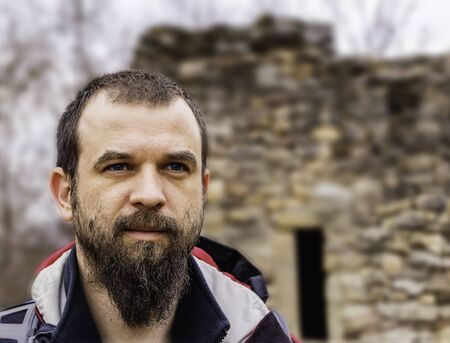 Blue eyed bearded man closeup in front of a stone ruined castle.