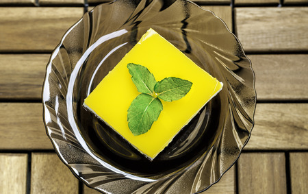 jello: Top view of chocolate sponge cheese cream filling and orange juice jello topping cake decorated with mint leaves.