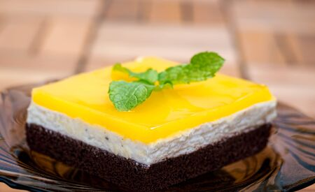jello: Lateral view of chocolate sponge, cheese cream filling and orange juice jello topping cake decorated with mint leaves. Stock Photo