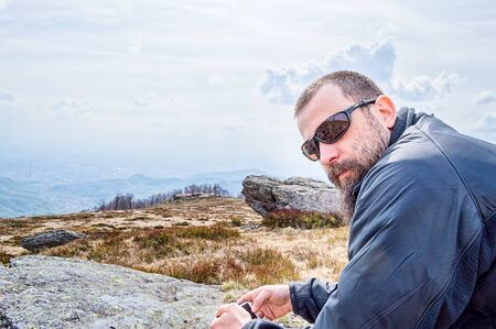 mountainscape: Bearded young man with sunglasses resting on top of the mountain with smartphone in his hands.