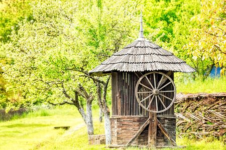 wood agricultural: Old wooden water well house with a large wheel near a woven willow fence with green trees in the background. Stock Photo