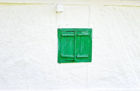 whitewashed: Closed green wooden window shutters on an old whitewashed wall.