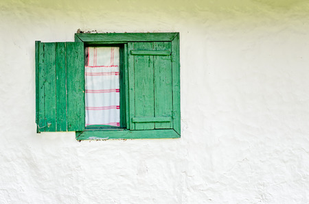 red shutters: Half open old window with wooden shutters and a handmade white and red curtains. Stock Photo