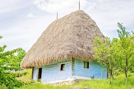 thatched roof: Light blue old clay house with a thatched roof, exposed wooden beams and stone foundation.