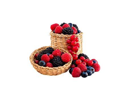 bounty: Frambuesas, moras, arándanos y grosellas rojas en y alrededor de una cesta de mimbre con tapa aislado en blanco.