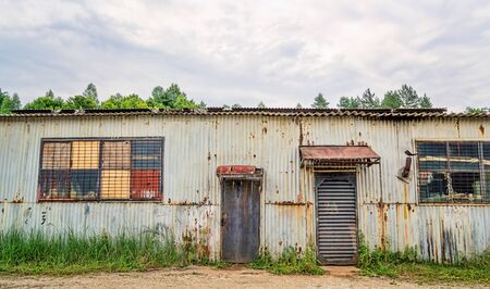 ruinous: Rusty old improvised shed made of sheets of corrugated iron. Stock Photo