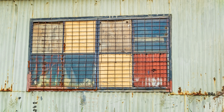 corrugated iron: Window detail of a rusty old improvised shed made of sheets of corrugated iron.