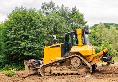 ripper: Yellow and black small bulldozer covered in mud.