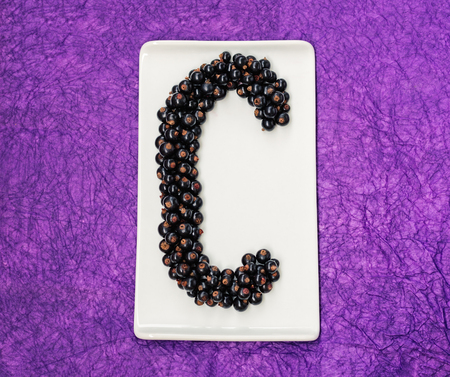 Letter C made of rows of blackcurrants on a rectangular white plate against a purple background.
