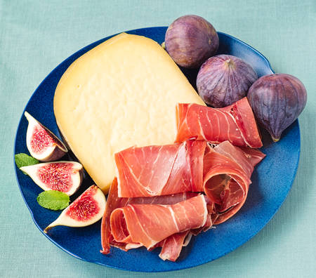 quartered: Serrano cured ham with hard cheese, quartered figs and mint leaves. Stock Photo