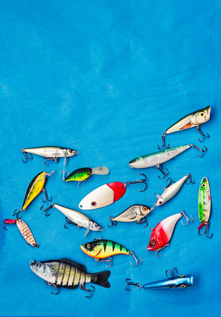 Miscellaneous collection of fishing lures against a blue background.