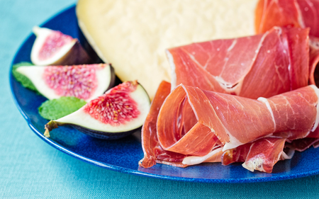 Serrano cured ham with hard cheese, quartered figs and mint leaves. Reklamní fotografie