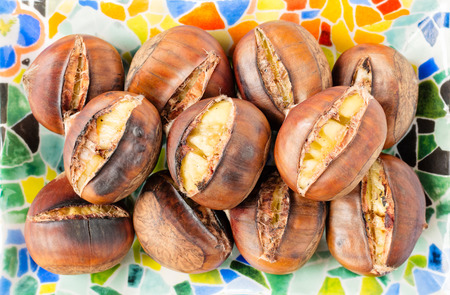 paleolithic: Top view of roasted chestnuts in their shells on a colorful mosaic plate.