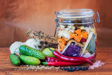 Jar of assorted brined lacto-fermented pickles on a wooden table surrounded by vegetables and spices. Reklamní fotografie - 48095816