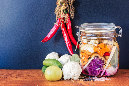 ferment: Jar of assorted brined lacto-fermented pickles on wooden table. Stock Photo