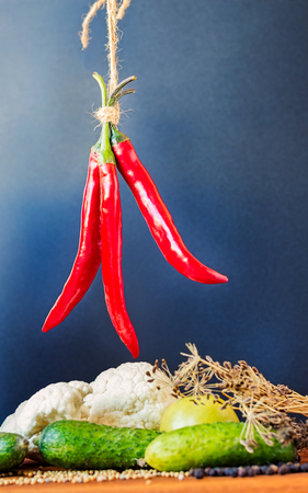 chiles picantes: Three red hot peppers hanging to dry above vegetables.