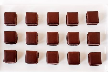 chocolate truffles: Top view of rows of  milk chocolate truffles against a white background.
