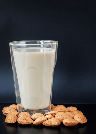 intolerant: Almond milk in a double wall insulated drinking glass with almond seeds in shells on a black table against a dark blue background Stock Photo
