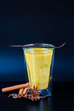 double glass: Turmeric infused almond milk in an insulated double wall glass with spices on a black table with vanilla pod on top.