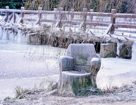 ice dam: Wooden chair carved from a tree stump near a frozen pond in front of a wooden bridge.