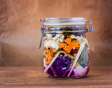 Jar of assorted brined lacto-fermented pickles on a wooden table.