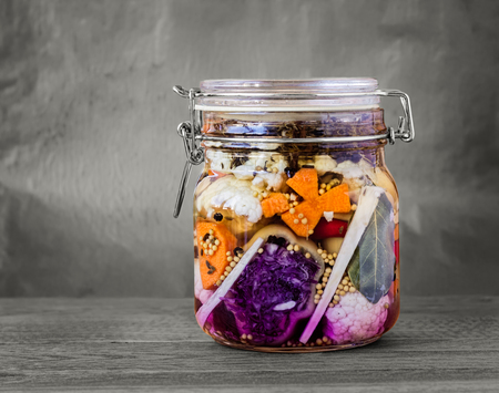 desaturated: Jar of assorted brined lacto-fermented pickles on a wooden table with desaturated background. Stock Photo