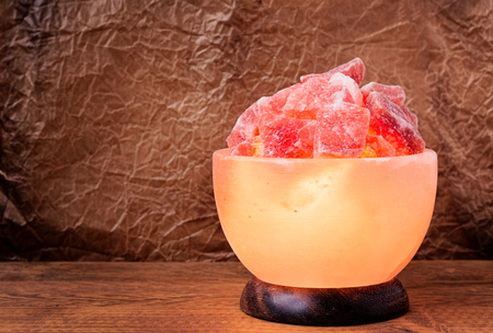himalayan salt: Turned on Himalayan pink salt lamp carved as a bowl on a wooden table with wrinkled parchment paper background. Stock Photo