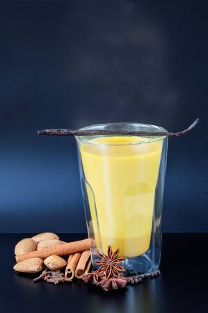 double glass: Turmeric infused almond milk in an insulated double wall glass with spices on a dark table.