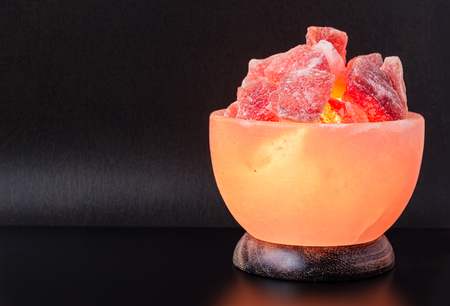 salt lamp: Turned on Himalayan pink salt lamp carved as a bowl on a black table with vintage textured dark grey background.