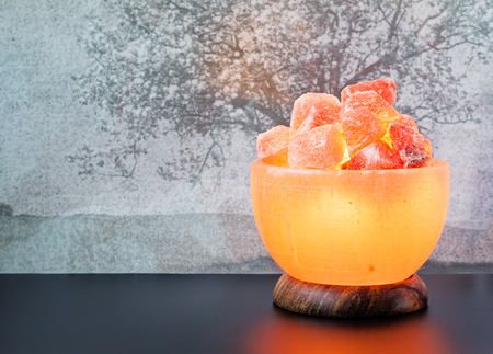 salt lamp: Turned on Himalayan pink salt lamp carved as a bowl on a black table.