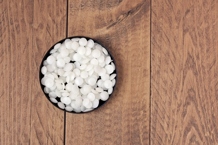 Top view of white cosmetic beeswax pellets in a black container on a wooden table. Reklamní fotografie