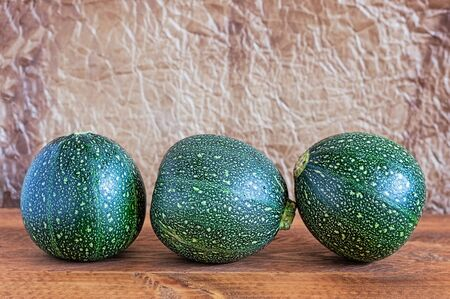 bola ocho: Three Eight ball squashes on a wooden table with brown wrinkled parchment paper background.