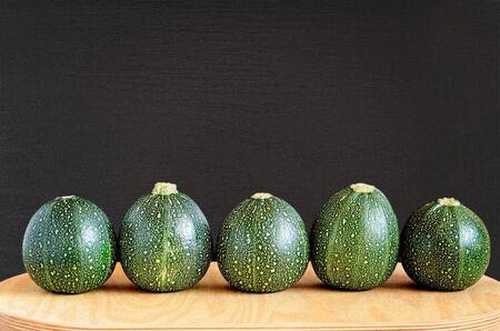 bola ocho: Cinco calabazas ocho bolas primas en una fila en una tabla de madera natural contra un fondo negro con textura de madera. Foto de archivo