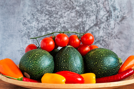 bola ocho: Selection of eight ball zucchini, cherry tomatoes, chili peppers and yellow, orange and red peppers on a bamboo plate.