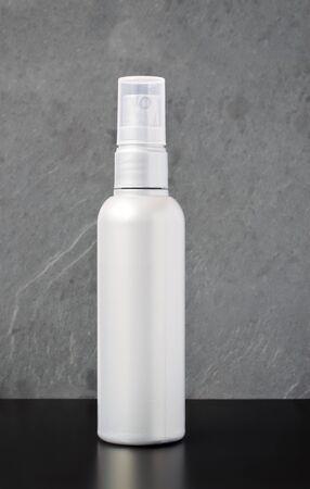 Silberne Plastiksprühflasche auf einer dunklen Tabelle mit grauem strukturiertem Hintergrund