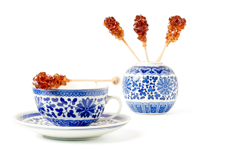 Blue pattern painted vintage cup of tea with brown sugar stirrer on top isolated on white.