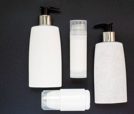 Top view of four beauty products in plastic bottles on a dark, grainy background. Reklamní fotografie
