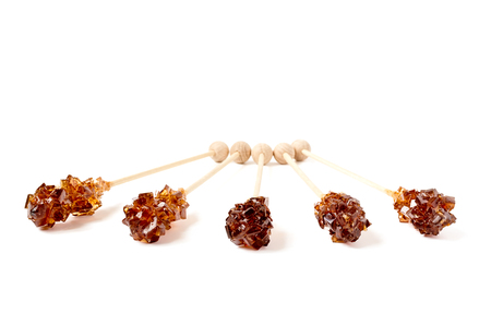 sweeten: Five brown sugar stirrers isolated on white.
