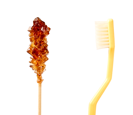 stirrer: Close up of a brown sugar stirrer facing a natural bristle toothbrush isolated on white. Stock Photo