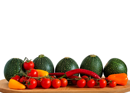bola ocho: Selection of eight ball zucchini, cherry tomatoes, chili peppers and yellow, orange and red peppers on a wooden board isolated on white. Foto de archivo