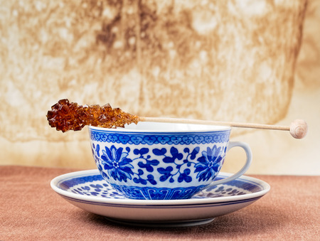 stirrer: Blue pattern painted vintage cup of tea with brown sugar stirrer on top Stock Photo