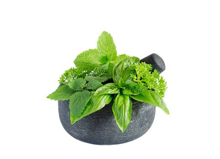 Gray granite mortar and pestle with herbs inside isolated on white