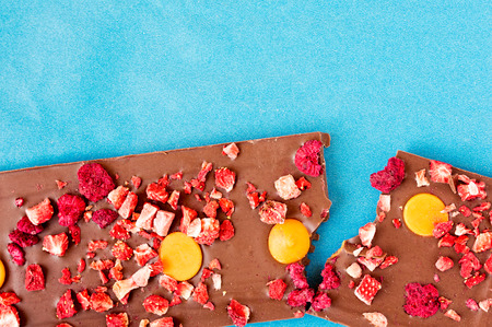 Top view of an orange, strawberry and raspberry milk chocolate tablet broken in two pieces on a cyan background.