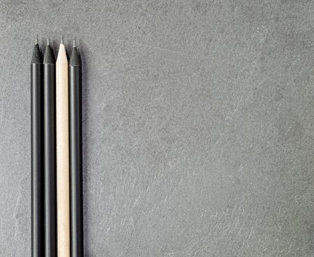light slate gray: Light colored pencil among three black ones on a gray granite slate.