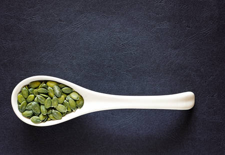Raw pumpkin seeds in a porcelain spoon an a dark textured background