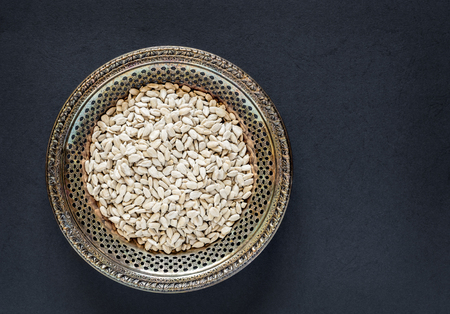 Antique metal bowl of raw dehulled sunflower seeds on a dark textured background